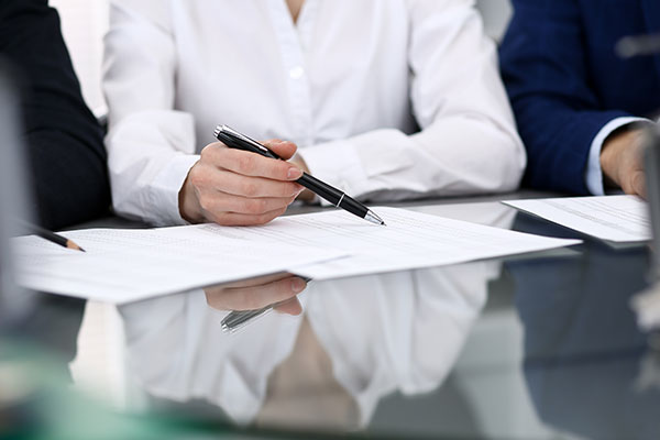 Business woman holding a pen and looking over paperwork