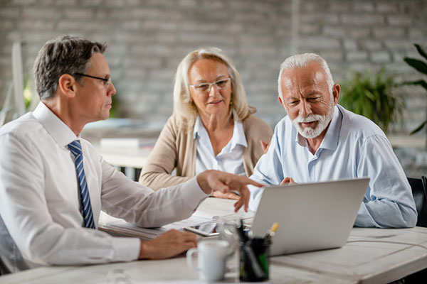 Businessman meeting with clients while using a laptop